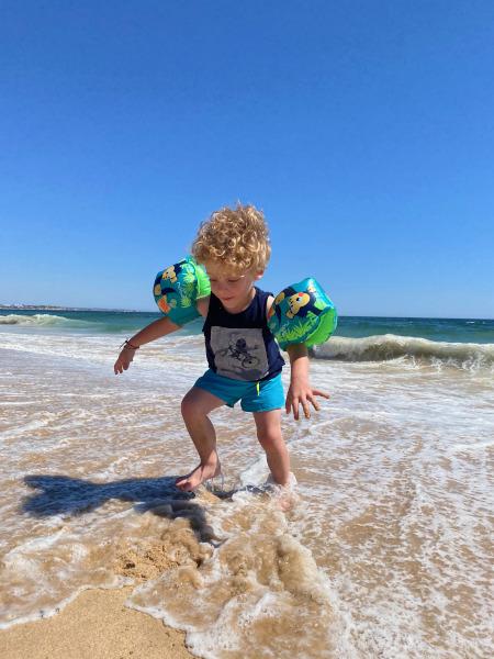 bambino corre tra le onde